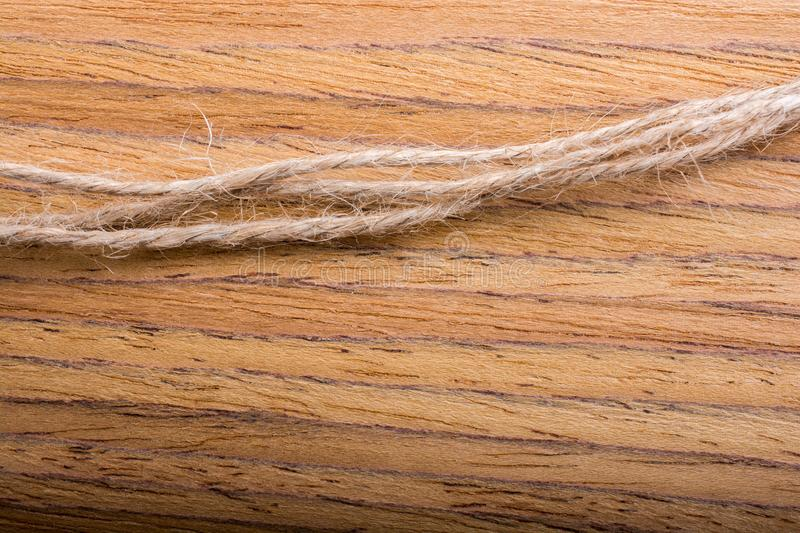 Linen thread strings placed on wooden texture stock image
