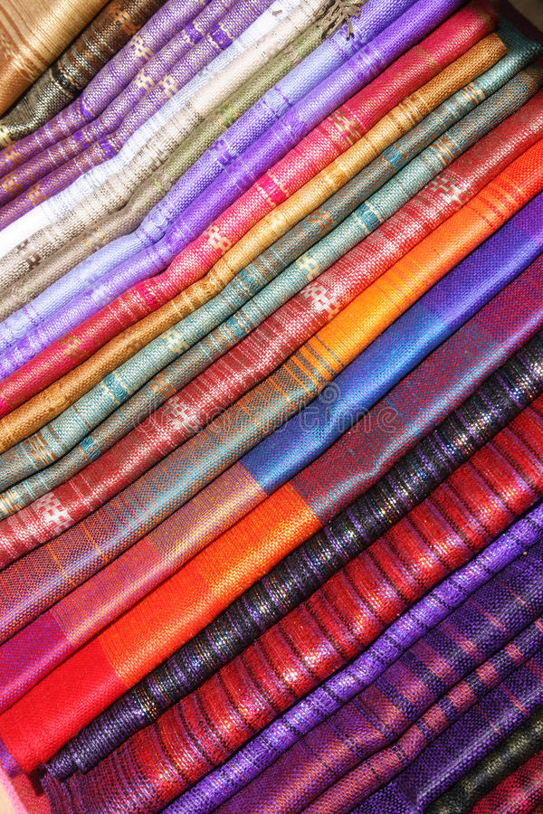 Linens at the Otavalo Craft Market. Handmade table linens in a wide assortment of colors and patterns are stacked for sale in an outdoor craft market in Otavalo royalty free stock image