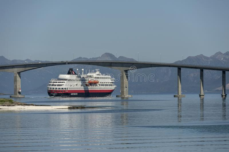 Liner cruising under high bridge near Stokmarknes, Norway. STOKMARKNES, NORWAY - July 08 2019: view of coastal liner cruising under high concrete bridge, shot on stock photos