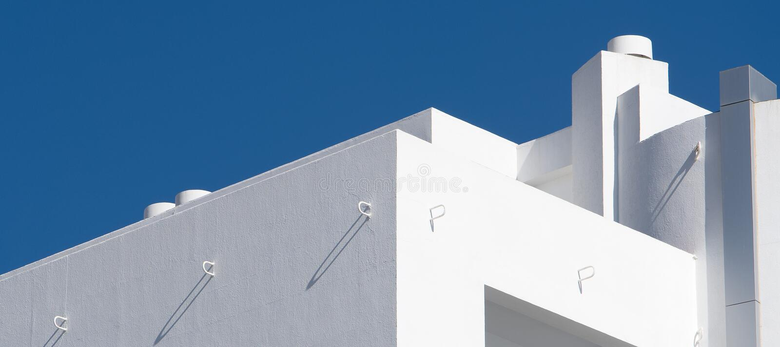Lines and angles of modern building. Abstract. The lines and angles at the top of a modern building, contrasting with the beautiful blue  Mediterranean sky royalty free stock photos