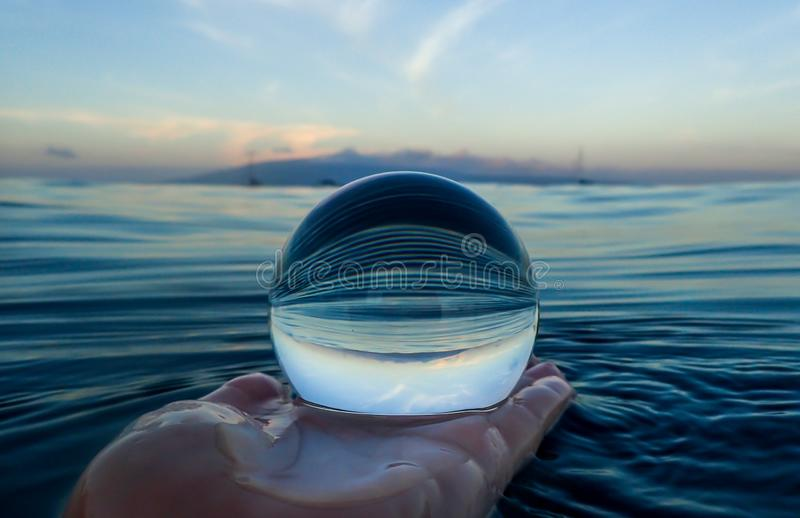 Blue Ripples on Ocean Surface Captured in Glass Ball. Lines created by ocean surface with island on horizon captured in close up glass ball stock photos