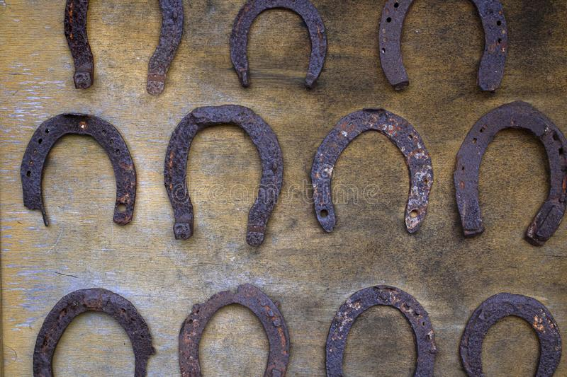 Lines on many old rusty metal horseshoe hanging on an old wooden surface. Horizontal. Lines on many old metal rusty horseshoe hanging on an old wooden surface stock image