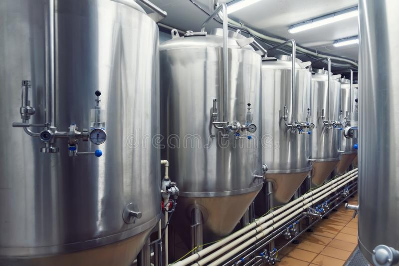 Lines of metal tanks in modern brewery. Shopfloor with brewery facilities. Manufacturable process of brewage. Mode of beer product. Ion. Brewing. Inside view of stock images