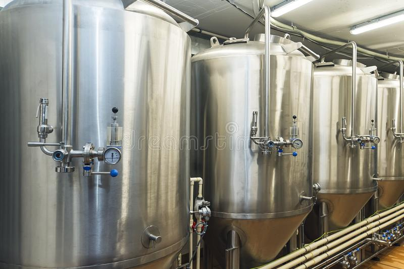 Lines of metal tanks in modern brewery. Shopfloor with brewery facilities. Manufacturable process of brewage. Mode of. Beer production. Industry. Inside view of royalty free stock image