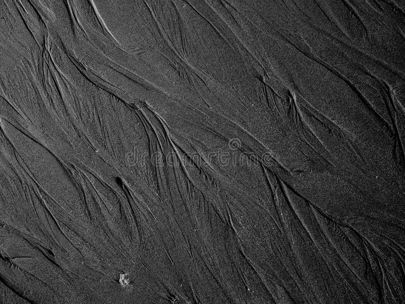 Lines in the sand. White lines in the black sand on a beach stock photo