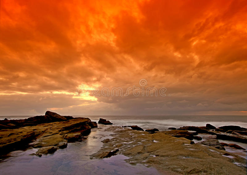 Lines to orange sky seascape. This photo captured the incredible dawn colours in the sky and sea before the sun rose above the horizon, turning the sky a stock image