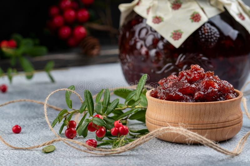 Lingonberry jam or sauce in wood bowl and in a glass jar with cranberries, cowberries on wood background stock photography