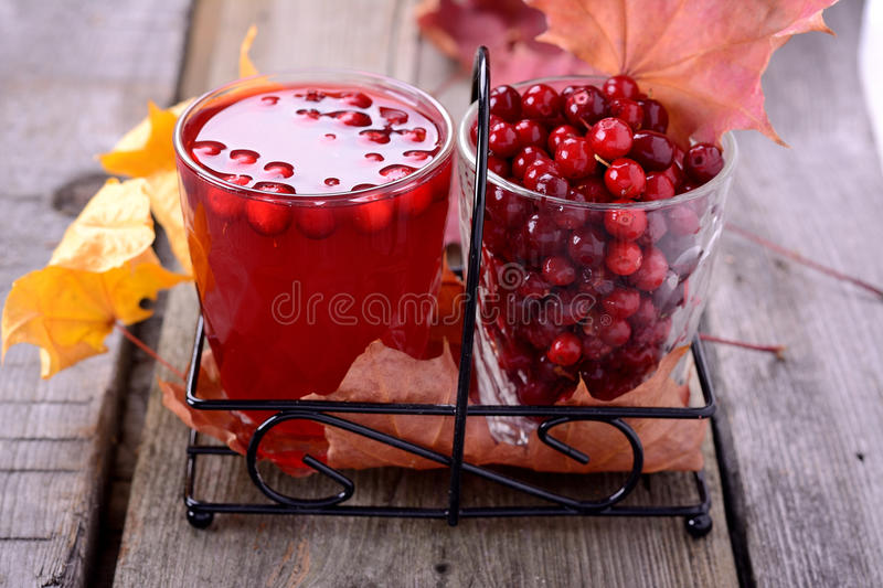Lingonberry juice and berries. On old wooden table royalty free stock photo