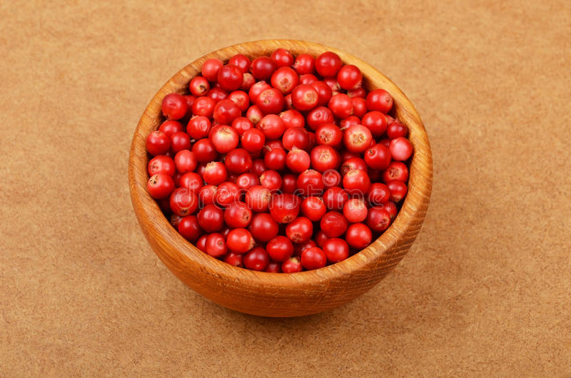 Lingonberry (Vaccinium vitis-idaea). In dish on wooden background stock photography