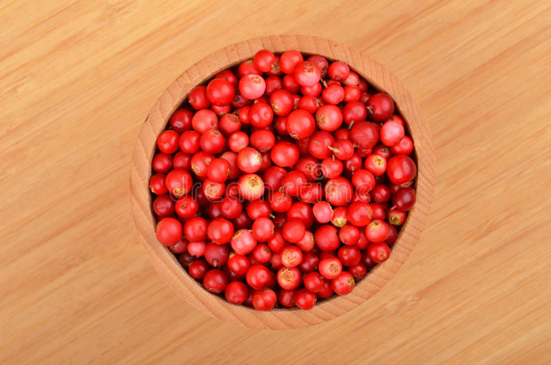 Lingonberry (Vaccinium vitis-idaea). In dish on wooden background royalty free stock images