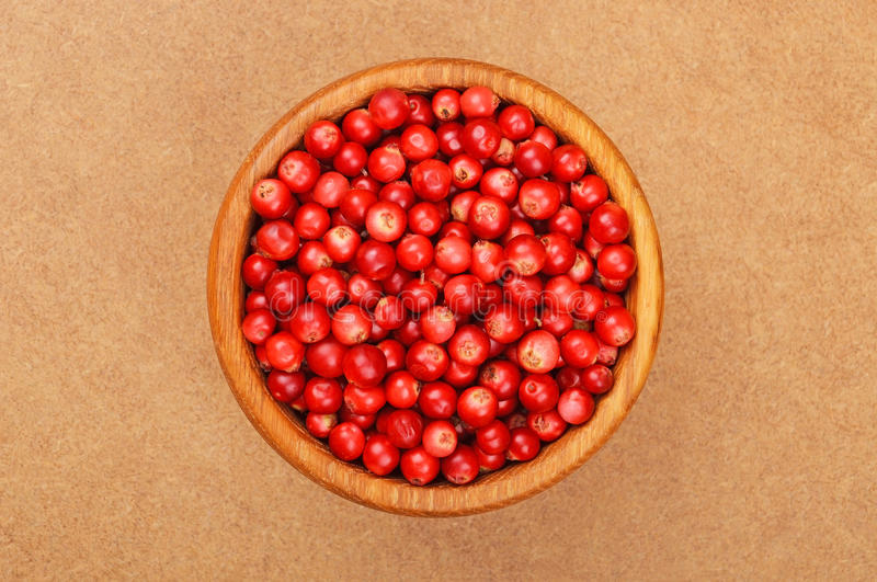 Lingonberry (Vaccinium vitis-idaea). In dish on wooden background stock photo