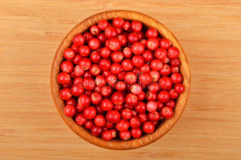 Lingonberry (Vaccinium vitis-idaea). In dish on wooden background stock photos