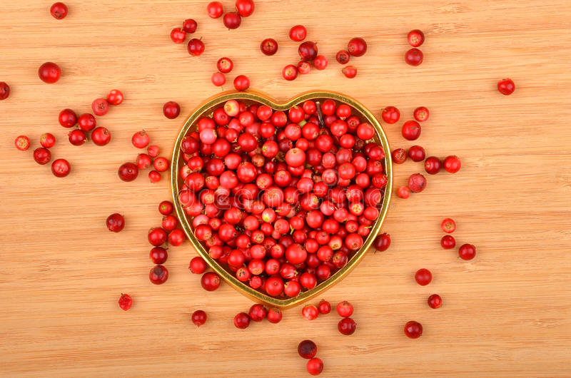 Lingonberry (Vaccinium vitis-idaea). In heart shape form on wooden background stock images