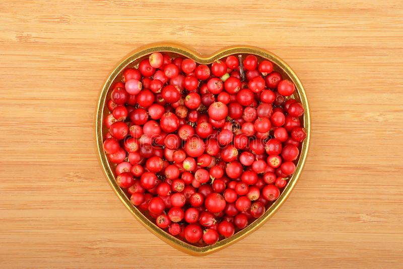 Lingonberry (Vaccinium vitis-idaea). In heart shape form on wooden background royalty free stock images