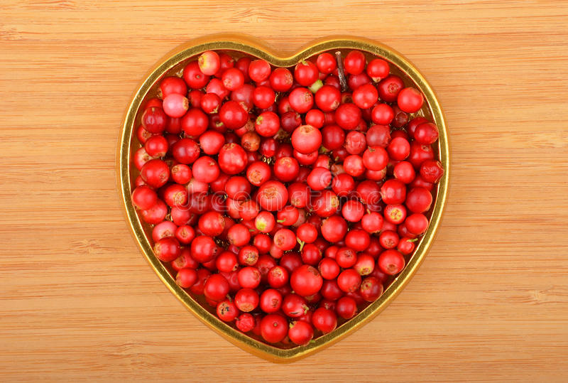 Lingonberry (Vaccinium vitis-idaea). In heart shape form on wooden background stock photo