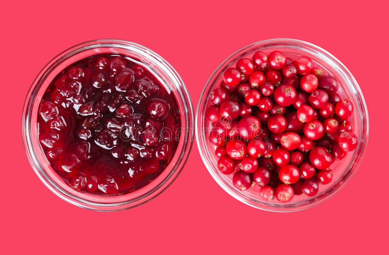 Lingonberryjam en lingonberries in glaskommen over roze stock foto