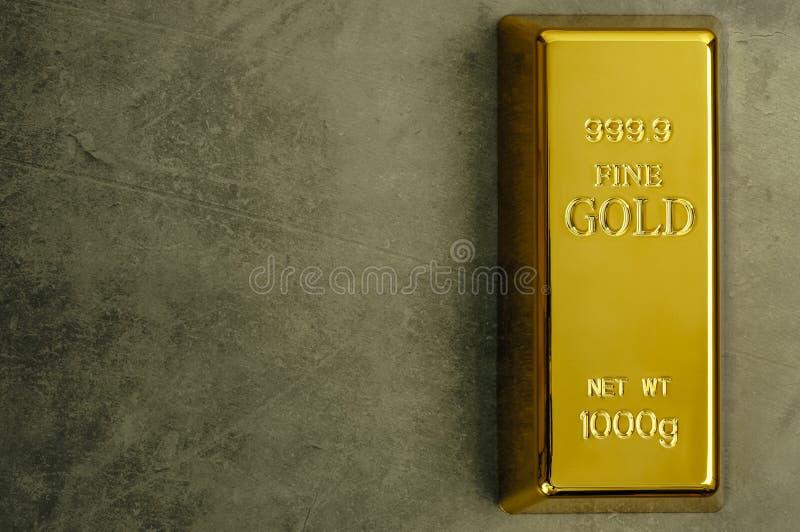 Lingote de lingote puro do metal do ouro em um fundo textured cinzento imagens de stock royalty free