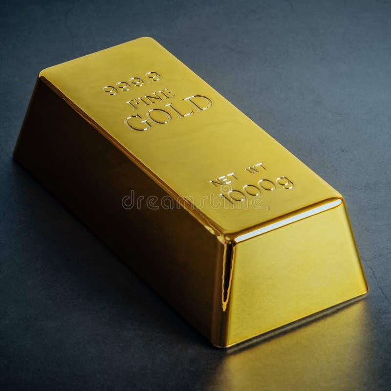 Lingote do lingote da barra de ouro no fundo azul Localizado diagonalmente imagem de stock royalty free