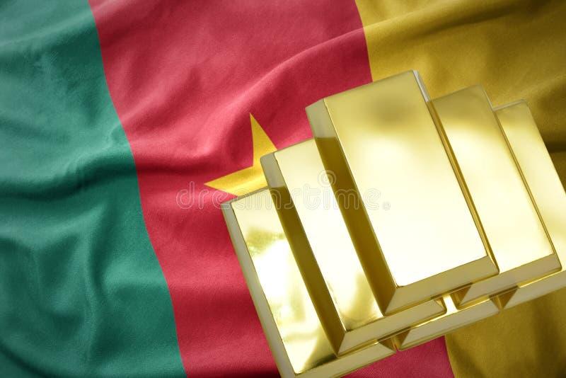 Lingotes de oro brillantes en la bandera del Camerún fotografía de archivo libre de regalías