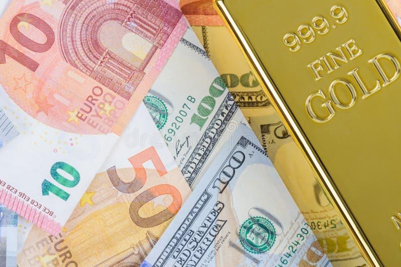 Lingotto del lingotto della barra di oro contro lo sfondo delle fatture dell'euro e del dollaro immagini stock libere da diritti