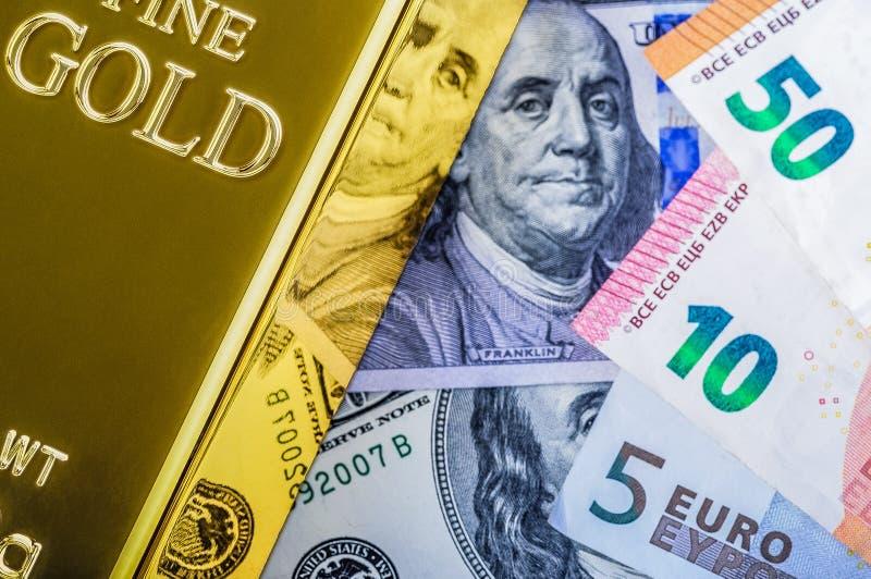 Lingotto del lingotto del metallo dell'oro sui precedenti delle fatture dell'euro e del dollaro fotografia stock libera da diritti