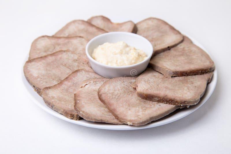 Lingua bollita manzo con rafano su un piatto bianco fotografia stock
