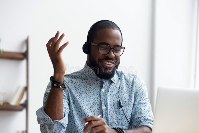 Lingua straniera di pratica nera del giovane facendo uso del computer portatile fotografia stock