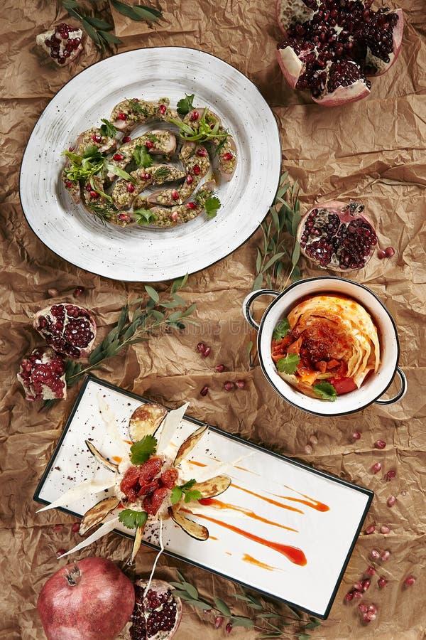Lingue dell'agnello con il melograno, il cavolo marinato ed i hummus con melanzana fotografie stock