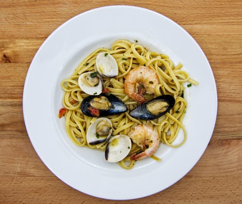 Linguine allo scoglio, naczynie włoski makaron z owoce morza na drewnianym stole zdjęcia royalty free