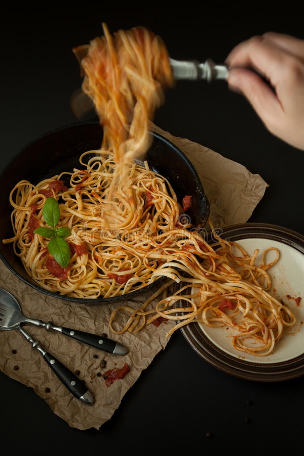 Linguine with Basil and Red Sauce in Cast Iron Pan Being Served royalty free stock photos