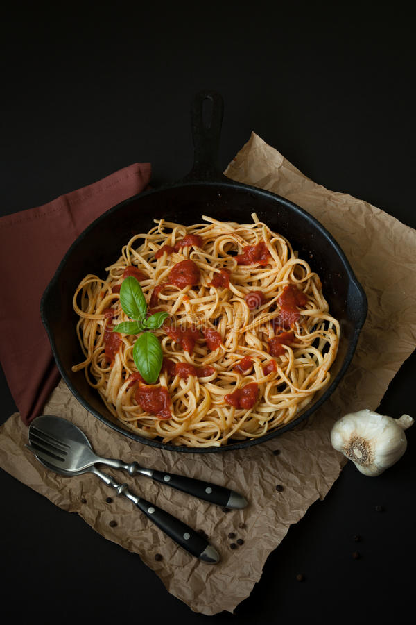 Linguine with Basil and Red Sauce in Cast Iron Pan royalty free stock image