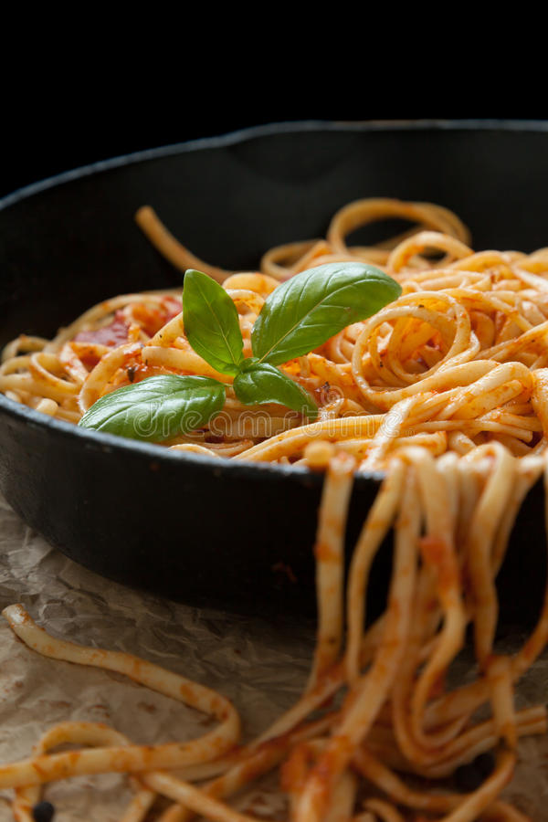 Linguine with Basil and Red Sauce in Cast Iron Pan stock photos