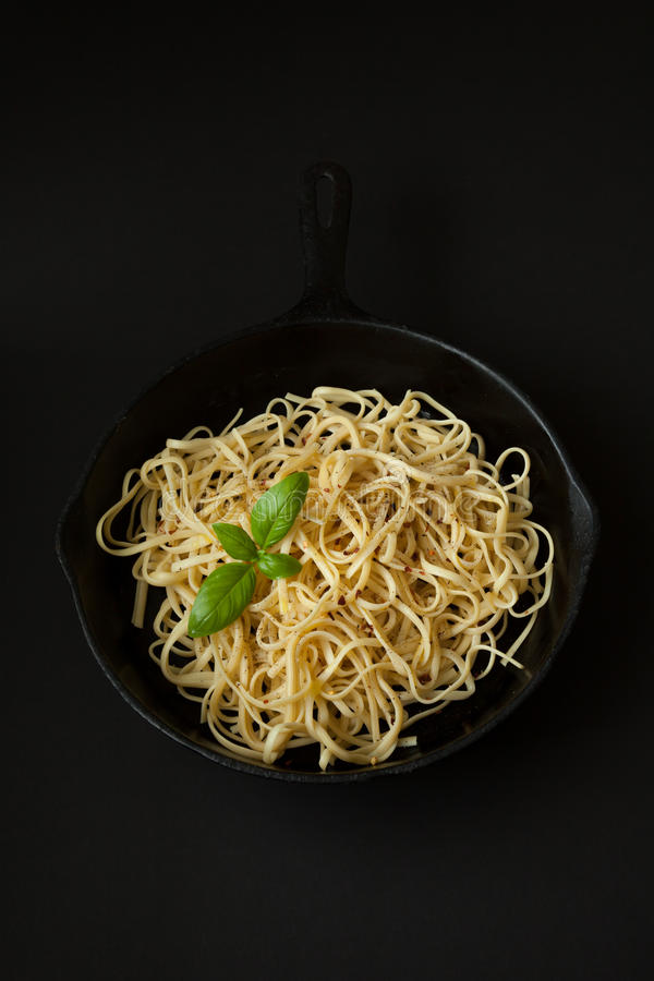 Linguine in a Cast Iron Pan with Basil on Black Background stock image
