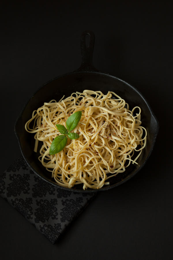 Linguine in a Cast Iron Pan with Basil on Black Background royalty free stock photo