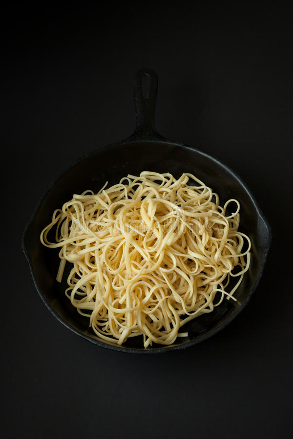 Linguine in a Cast Iron Pan with Black Background royalty free stock images