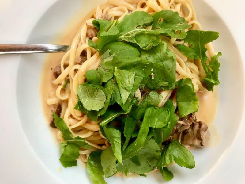 Linguini-Teigwaren mit Lamm-Fleisch, Sahnesauce und Arugula, Rocket oder Rucola-Blätter lizenzfreies stockfoto