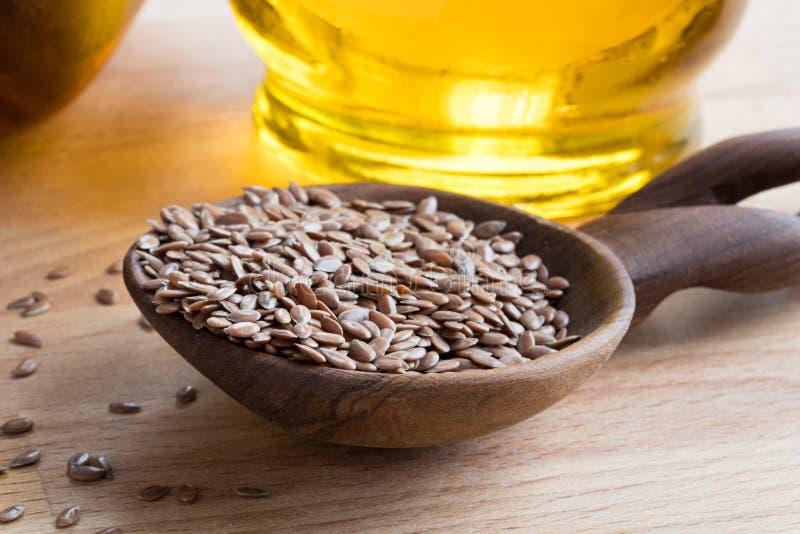 Linhaça em uma colher de madeira, com óleo de flaxseed no fundo fotos de stock