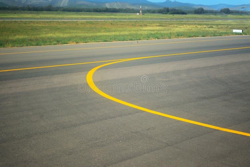 Linha amarela em um taxiway do aeroporto fotografia de stock royalty free