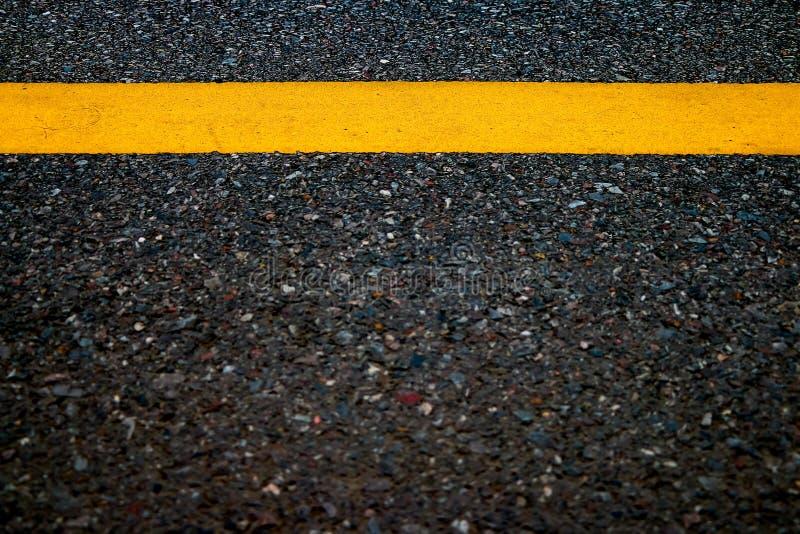Linha amarela no fundo da textura da estrada, foto de stock
