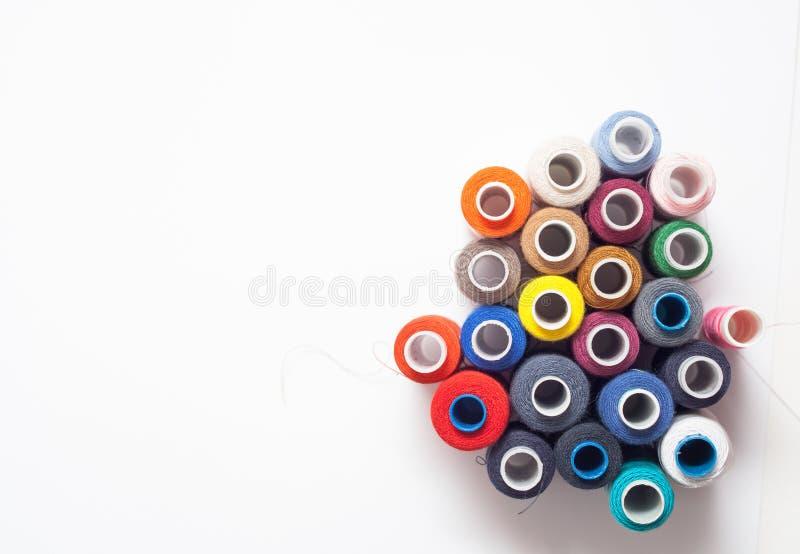 A linha colorida bobina no fundo branco, costurando ferramentas fotos de stock