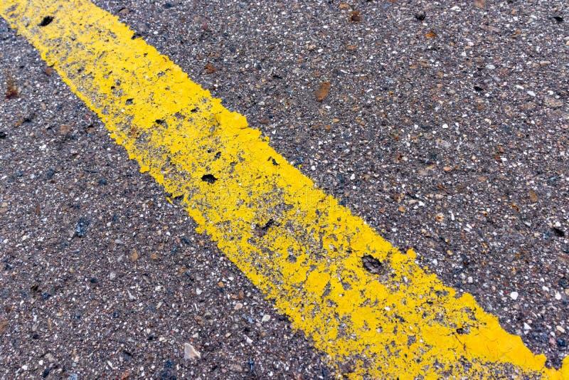 Linha contínua amarela, marcação de estrada do grunge única no asfalto, fundo com espaço da cópia foto de stock