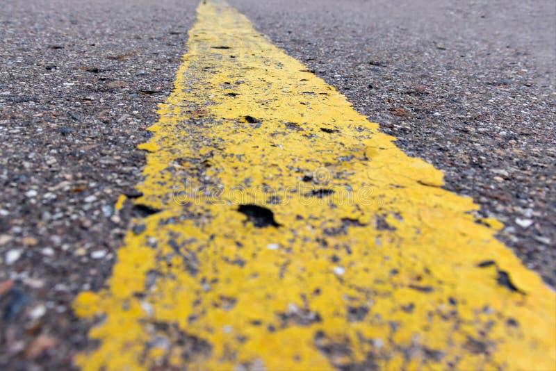 Linha contínua amarela, marcação de estrada do grunge única no asfalto perto acima, fundo com espaço da cópia fotos de stock royalty free
