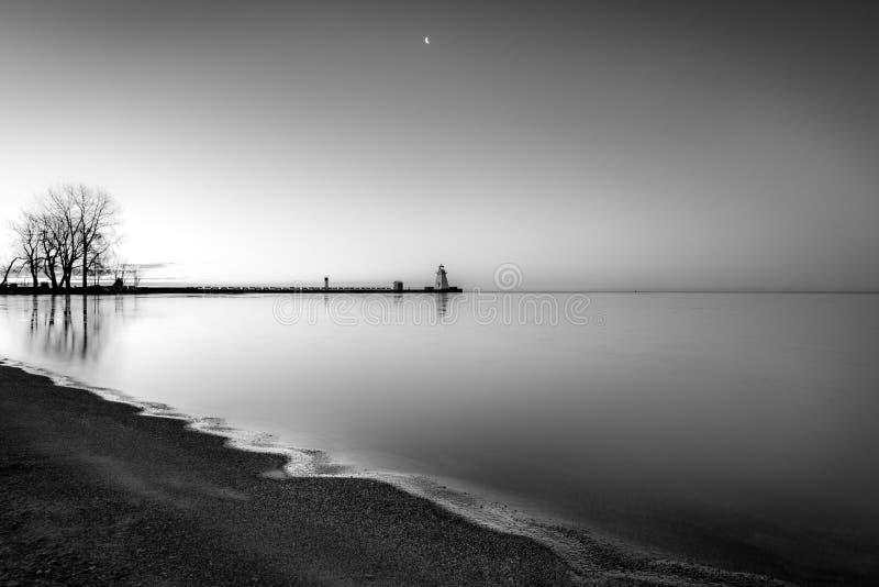 Linha costeira calma temperamental com águas imóveis que refletem no morni adiantado imagem de stock royalty free