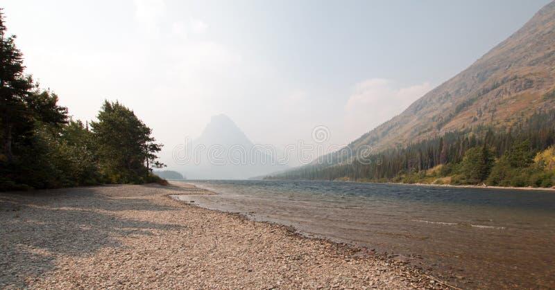 Linha costeira gravelosa de lago medicines da parte superior dois no parque nacional de geleira durante os 2017 incêndios florest foto de stock