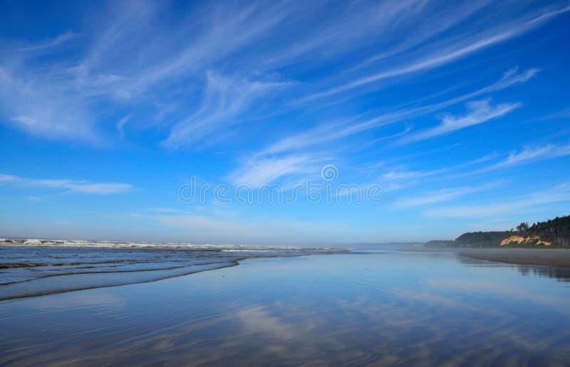 Linha costeira noroeste pacífica da praia do oceano Nuvens que refletem na areia molhada fotografia de stock