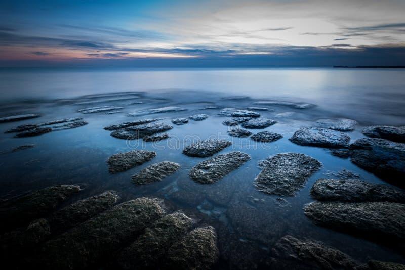 Linha costeira rochosa durante o por do sol no Lago Ont?rio imagem de stock royalty free
