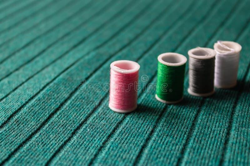 Linha costurando cor-de-rosa com outras linhas coloridas no fundo verde de matéria têxtil - imagem foto de stock royalty free