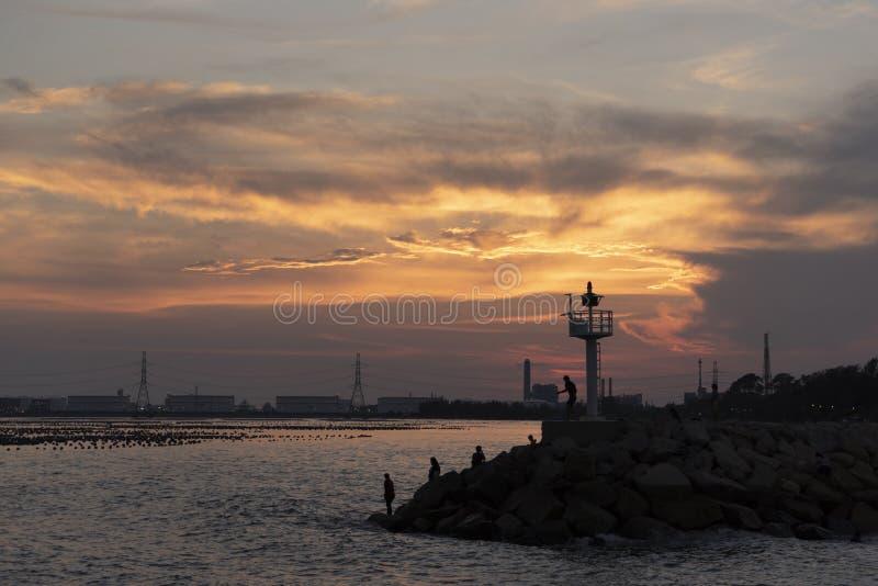 Linha da rocha do quebra-mar com a casa clara contra a luz do por do sol fotografia de stock royalty free