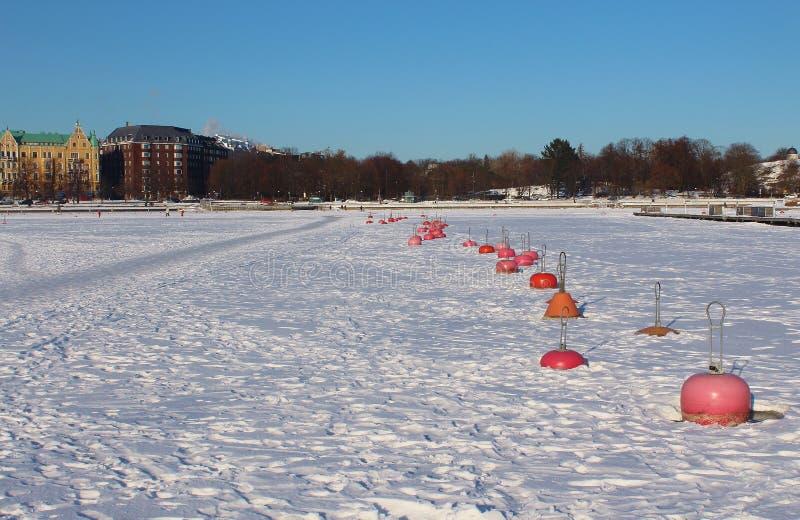 Linha de boias no mar Báltico congelado, Helsínquia, Finlandia imagens de stock