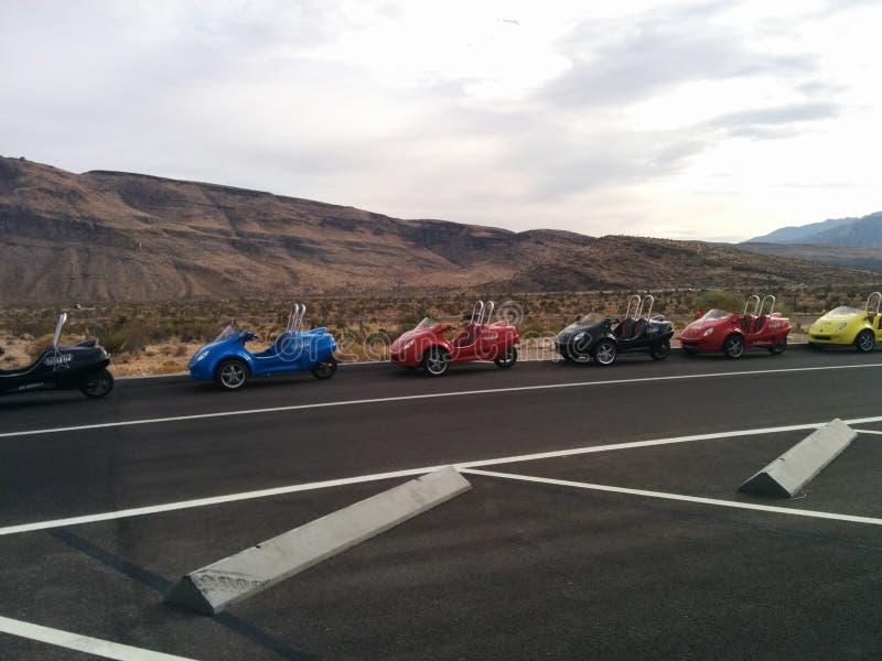 Linha de carros do 'trotinette' de dois-Seat no parque de estacionamento com paisagem da montanha foto de stock